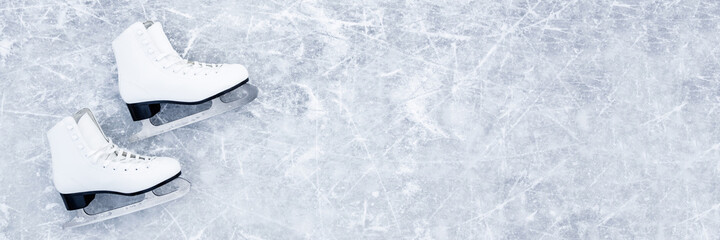 White female figure skates on ice background. Sport accessories for outdoor activities in cold winter season. Closeup. Empty place for text. Wide banner. Top down view.