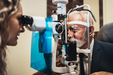 Elegant Senior Bearded Man Receiving Ophthalmology Treatment. Doctor Ophthalmologist Checking His Eyesight With Modern Equipment.
