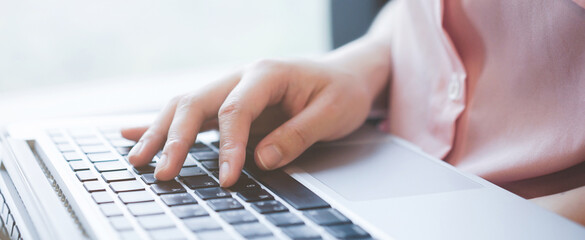 Midsection Of Woman Using Laptop On Table