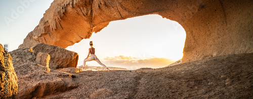 Obraz Woman doing yoga, stretching, meditating on the top of a mountain above clouds at sunrise. Zen, meditation, peace of mind concept. Travel. Beauty in nature. - fototapety do salonu