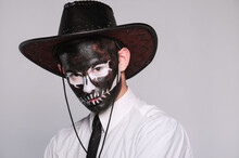 A Man In Halloween Makeup As A Dead Man With A Black Skull In A Cowboy Hat And Tie