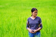 Leinwandbild Motiv Young Woman Photographing With Camera While Standing At Rice Paddy