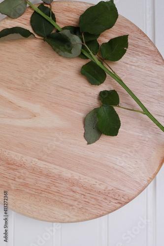 Fototapeta łodyga róży z liśćmi na drewnianej desce obraz