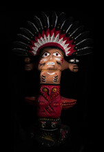 A Statuette Of A Magical Character, A Protective Totem Of A Pagan Image And Religion, On A Dark Background