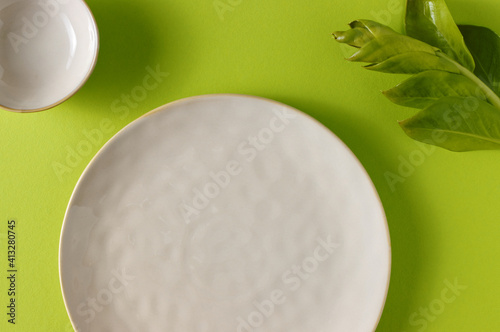 Empty stoneware plate at green spring table Fotobehang