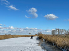 Couple Ice Skating On A Frozen Canal In Friesland