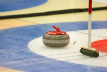 Close-up Of Curling Stone And Curling Broom On Table