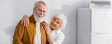 Smiling Elderly Woman Hugging Husband In Kitchen, Banner