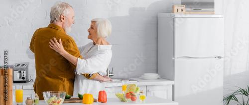 Obraz Positive elderly couple hugging near ripe vegetables on kitchen table, banner - fototapety do salonu