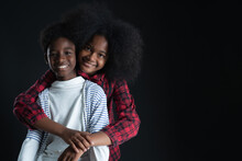 African Teen Siblings Boy And Girl Hugging With Smiley Face On Black Background. Older Sister Back Hug Her Brother. Good Family Relationship Concept