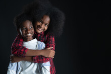 African Teen Siblings Boy And Girl Hugging With Smiley Face On Black Background. Older Sister Hug Her Younger Brother From Behind. Good Family Relationship Concept