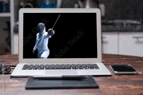 Fototapeta The fencer moves forward with a sword in his hand. Sport concept.