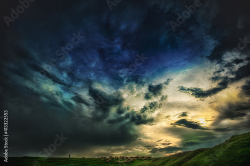 Obraz na plátně Breathtaking view of dramatic sunset sky with a shepherd and a herd of sheep on