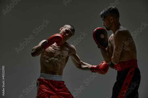 Fototapeta Boxers athletic males in boxing gloves fighting during workout on gray studio ba