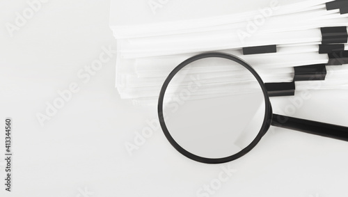 Fotografia, Obraz Stack of report paper documents with magnifying glass
