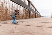 Miniature Figurine On A Wooden Pier Taking Photos With A Camera