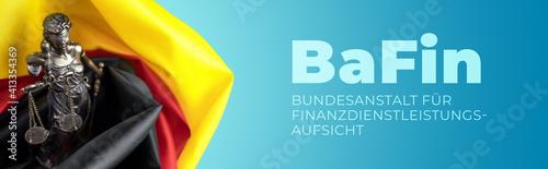 Fototapeta BaFin - Finanzaufsicht. Justitia Skulptur umgeben von einer Deutschland Flagge. Text auf blauem Untergrund. obraz