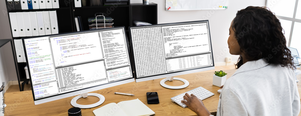 Fototapeta African Coder Using Multiple Computer Screens