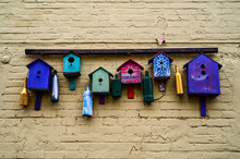 Multicolored Art Birdhouses Composition On The Brick Wall. Curious Installation Of Wooden Bird Nests On The House. Selective Focus.