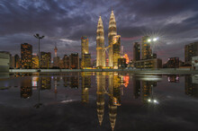 Reflection Of Illuminated Petronas Towers In River Amidst Buildings Against Cloudy Sky At Dusk