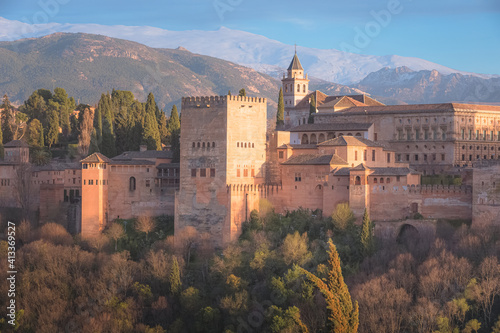 Classic view with sunset or sunrise golden light of Charles V Palace, the iconic Alhambra and Sierra Nevada Mountains from Mirador de San Nicolas in the albaicin old town of Granada, Andalusia, Spain.