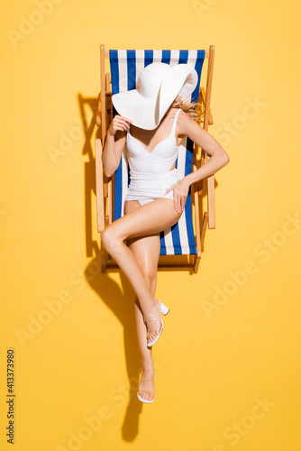 Fényképezés top view of slim woman in swimsuit obscuring face with straw hat while sitting in deck chair on yellow