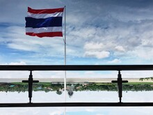 Upside Down Image Of Flag Reflecting On Calm Lake Against Cloudy Sky