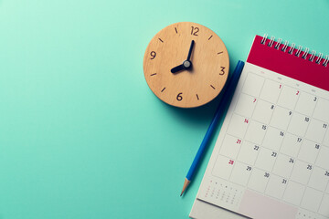close up of calendar, pencil and alarm clock on the green table background, planning for business meeting or travel planning concept