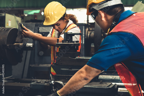 Fototapeta Group of skillful workers using machine equipment in factory workshop . Industry and engineering people technology concept . obraz