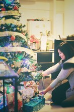 Smiling Woman Decorating Christmas Tree At Home