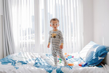 Cute Little Boy Toddler Standing On Bed In Room At Home And Looking At Camera. Adorable Innocent Baby Child In Nursery Room Staring And Watching. Lonely Kid Playing Alone At Home.