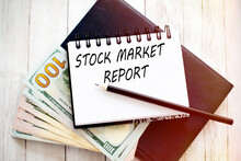 TOCK MARKET REPORT Text Written On Notebook With Dollar Bills And Pencil. Financial Concept