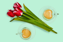 A Bouquet Of Three Tulips And Two Cups Of Coffee On A Light Green Background.