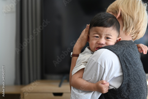 Image of Asian mother holding crying baby in comfortable home. Wallpaper Mural