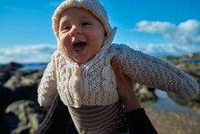 Baby Held And Lifted By Mother On The Beach In Winter