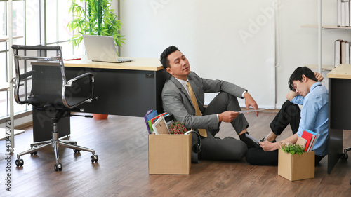 Fototapeta Senior and junior businesspeople wearing protective hygiene mask with box of belongings sitting and hopeless talk with sad and disappointment