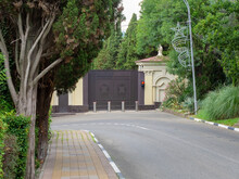Private Railway Gate With Traffic Lights And Automatic Bollards Surrounded By Green Trees Located Near The Road