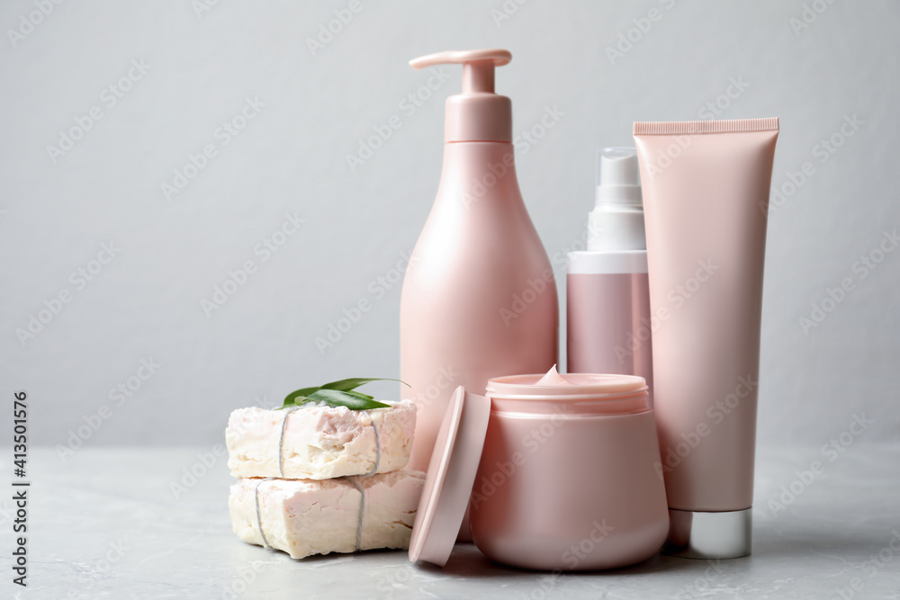 Fototapeta Set of hair care cosmetic products and soap bars on light grey marble table