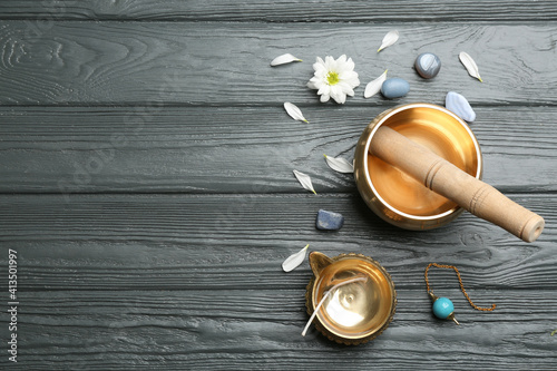 Flat lay composition with golden singing bowl on grey wooden table, space for text Fotobehang