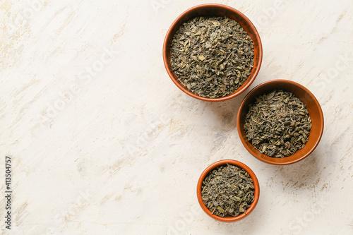 Fototapeta Bowls with dry tea leaves on light background obraz