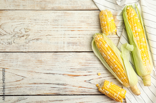 Fototapeta Tasty sweet corn cobs on white wooden table, flat lay. Space for text obraz