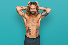 Handsome Man With Beard And Long Hair Standing Shirtless Showing Tattoos Doing Bunny Ears Gesture With Hands Palms Looking Cynical And Skeptical. Easter Rabbit Concept.