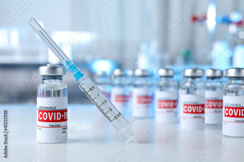 Slika na platnu Glass vial with COVID-19 vaccine and syringe on light table