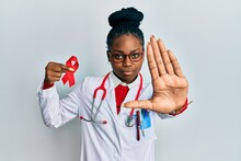 Young African American Woman Wearing Doctor Uniform Holding Support Red Ribbon With Open Hand Doing Stop Sign With Serious And Confident Expression, Defense Gesture