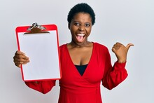 Young African Woman With Short Hair Holding Clipboard With Blank Space Pointing Thumb Up To The Side Smiling Happy With Open Mouth