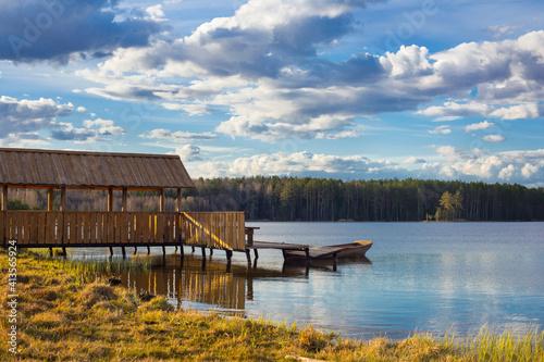 Fototapeta wooden arbor and pier on  shore of  spring lake