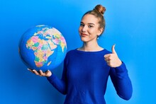 Young Blonde Woman Holding World Ball Smiling Happy And Positive, Thumb Up Doing Excellent And Approval Sign