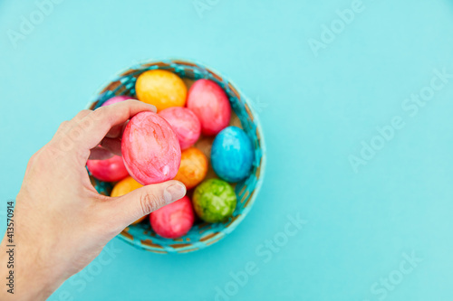 Fotografie, Obraz Cropped Hand Holding Easter Egg Against Blue Background