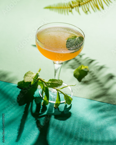 yellow tropical cocktail on a background of foliage, shadows from the sun. Green background © smirart