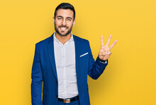 Young Hispanic Man Wearing Business Jacket Showing And Pointing Up With Fingers Number Three While Smiling Confident And Happy.